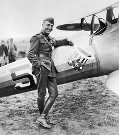 May 5, 1918: American aviator and lieutenant Eddie Rickenbacker (1890 - 1973), dressed in uniform, stands next to his World War I plane in a field near Toul, France.