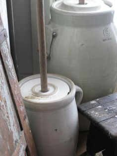 highbuttonshoe farmhouse. 2 large crock butter churns sit in a corner.