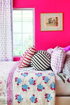 Bright pink wall paint balanced with softer bedding.