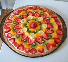 "Fruit pizza - ""I make mine with a sugar cookie dough crust and Tastefully Simples Strawberry Cheese ball as the base for the fruit.  You can add any fruit to top.  We are a berry family and use kiwis with strawberries, raspberries, blueberries,  blackberries and sometime bananas."""