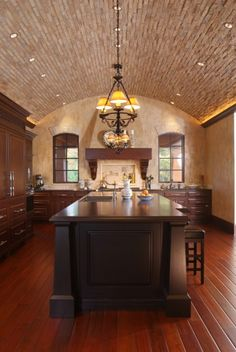 A kitchen features a dramatic brick barrel-vaulted ceiling arching over a large center island  (via Visbeen Associates, Inc.)
