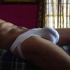 Guy laying on bed in jocksttrap