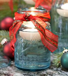 This pretty blue Ball jar is being used in a Christmas display, but switch the ribbon to a red bandana and use this outside for a patio table at a cookout....so cute!  If you don't have floating candles, put a clear votive cup in the bottom with a votive or tealight candle.....