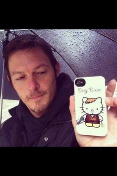Walking Dead's Darryl Dixon displays his Hello Kitty Phone. ~~~ this is the best thing I have ever seen in my life. Damn I love that show and Daryl and that Norman has this phone case of himself Hello Kitty Daryl... Just greatness