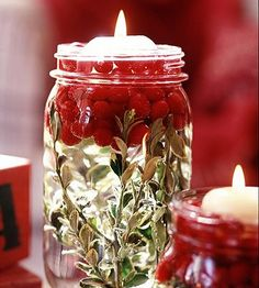 way cute table decoration for Christmas dinner mason jar, green leaves, cranberries, water, and floating candles!