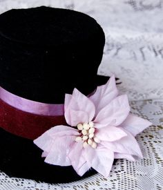 Mini Top Hat with Light Pink Flower and Dark Velvety Ribbon - Recycled by MuertoMarie, $28.00    This hat was crafted with love and care out of all recycled, re-purposed, and up-cycled materials to make it as green as possible.    The ribbon and flower have been reused from old fake floral arrangements so you can look good and feel ecologically responsible too!  Click on the photo for more!