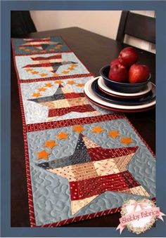 """Patchwork Patriotic Table Runner Pattern: Add some Americana to your summer table! This quick and easy table runner project features small wool felt stars around larger patchwork stars. This is a great way to use mini charm squares or jelly roll strips! Pattern includes all instructions for the 12 1/2"""" x 53"""" project. Designed by Jennifer Bosworth of Shabby Fabrics."""