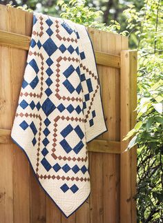 This classic and simple quilt features simple four-patch unit piecing in blue and brown solids. This quilt is the perfect template for experimenting with quilting. #classic #quilt #FonsandPorter #Quiltspiration