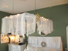 Window repurposed into bed canopy - I love this one, the white Christmas lights under the sheer fabric are just dreamy, and this can be added to any bed since it is hung from the ceiling (hmmm ... now I'm thinking white decorative chain, maybe just the tiniest-leaved ivy garland, or something with flowers ... wonder if that would detract from the canopy itself?) (LOTS of other great projects on the same page, best collection I've seen so far!) (~TA upcycle window & HD bed)