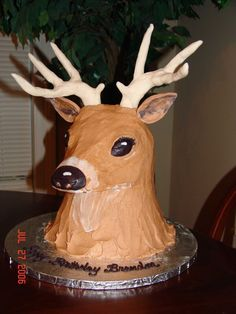 "All cake except for fondant antlers.      It is kindof difficult to describe how it was done, but I will try.  The neck is an upside down doll pan.  I placed dowel rods in this then cut a board for the snout and head to sit on top.  The head and snout are carved from 6"" round cakes put together.   I made the antlers way ahead of time with fondant so that they had time to dry hard.  The ears are also fondant.  The rest is just buttercream icing."