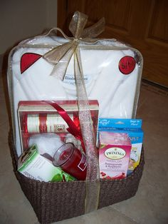 Homemade Mother's Day spa basket with bathrobe, hair towel/shower cap, body wash, lotions, loofah, candle, tea, and chocolate treats