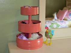 Beth managed this by upcycling some metal food tins and thrifted candlesticks.  She spray painted both the tins and candlesticks with Krylon's Coral Isle.  She glue the candlesticks to the bottom of each tin, stacking them from largest to smallest.  The end result is similar to a pretty cake stand, but with the additional storage capacity offered by the higher sides of the tins.