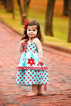 Cute little girl in aqua and red polka dot dress.