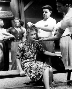 This girl pays the penalty for having had personal relations with the Germans. In the Montelimar area, France, French civilians shave her head as punishment. August 29, 1944.