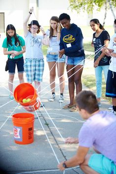 Have the team lift the bucket with rope and successfully pour each tennis ball into the other bucket.