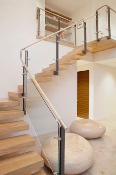 Awesome floating wood stairs and a sleek very well detailed glass / metal hand railing at a Luxury LEED home designed by  Maienza-Wilson Interior Design + Architecture
