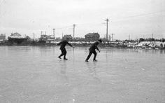 Two men skating on a frozen lake. It is believed to be Lake Holly at the Virginia Beach oceanfront - Virginia Beach, Virginia. (Date: 1900s - 1910s).