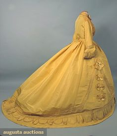 "PARIS YELLOW SILK PROMENADE DRESS, c. 1868  2 piece daffodil yellow & goldenrod faille, self-fabric half-circles alternating w/ pleated half-circles bound w/ yellow silk satin bands & trimmed w/ hand-made blonde bobbin lace (lace needs re-tacking in places), skirt w/ satin bows & trim,white muslin & silk bodice linings, ""Robes & Confections Merlot Larcheveque 21 Boulevard des Capuchines"", incl. white linen petticoat, B 41"", W 26.5"", front skirt L 43"", back L 67"", Hem C 194"","