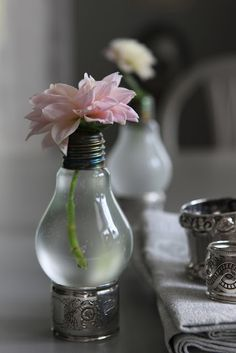 Cut the bottom of a used light bulb off and empty the bulb of its contents. Rinse it out with water (and maybe some soap) to clean out the metal. Next, fill it with water and then set it on something that will hope it upright, such as a napkin ring. Add your favorite flower to this mini vase for the completed look.  A few of these create a lovely centerpiece especially when they are set at various heights.