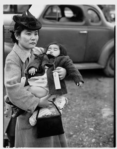 Fumiko Hayashida, a young mother of thirty-one, carries her 13 month-old daughter Natalie Kayo, holding her teddy bear, on March 30, 1942, along the Eagledale Ferry landing as she walked surrounded by armed soldiers to a waiting ferry on Bainbridge Island that would send her to Manzanar Internment Camp in California arriving by train on April 1, 1942. Photo for the Seattle Post-Intelligencer