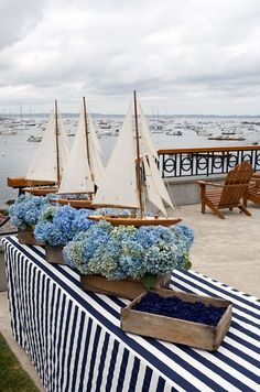 Entertaining at the beach - striped buffet tablecloth, blue hydrangeas, wooden model sailboats, adirondak chairs