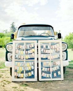 Paper-flag escort cards hang on two vintage windows, which are propped up against an old pickup truck