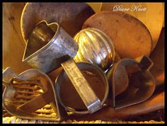 Farmhouse treasures, tin cookie and biscuit cutters and a tin mold in a basket of wooden butter paddles...