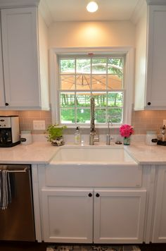 White cabinets, farmhouse style sink, and Cambria Torquay counters brought this kitchen up-to-date.
