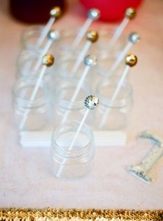 DIY cocktail drink twizzle sticks were made from lollipop sticks with wooden balls glued to the top. then glued sequin trim in gold and silver around them  via Ritzy Bee...love these for a New Year's party