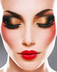 Gorgeous dramatic makeup look with black and gold eyes matched with red lips.