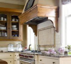 Painted lower cabinets and natural upper cabinets. Is that cedar? Lower cabinets are antique white. Wall is sand that looks taupe up higher. Lovely grey counters.
