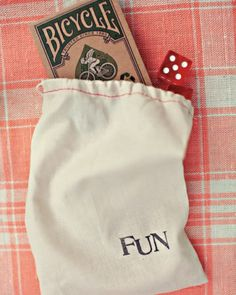 "Dinner Games: Dice and decks of cards packaged in muslin bags bearing the words ""fun"" or ""play"" served as tabletop icebreakers at the party."