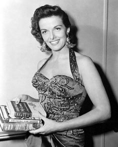 Jane Russell maybe at the public library. Russell (1921-2011) was signed by Howard Hughes for The Outlaw (1943), the film that was to make her famous. The film was not a classic by any means, but was geared to show off Jane's ample physical assets. Although made in 1941, it was not released until 1943 and then only on a limited basis due to the way the film portrayed Jane's figure. It was hard to pass the censorship board. When it gained general release in 1946, it was a smash at the box office.