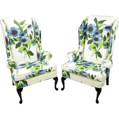 Pair 1960s Large Floral Linen Wing Chairs By Hickory  USA  Circa 1960s  Elegantly modern pair of wingback club chairs from Hickory Chair Company. The over sized floral print linen is comprised of green, blue red and black flowers on a white ground. The front legs are cabriole carved mahogany and the mahogany back legs have a slight curve.