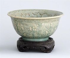 "LONGQUAN CELADON BOWL Ming Dynasty   In bell form. Decorated on the interior with an incised band of flowers about a chrysanthemum center. Rim decorated with lotus. Exterior decorated with relief passionflowers and lotus. Diameter 10 3/4"" (27.3 cm). Wood stand."