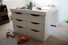 Kids Table - Activity & Storage - Great DIY lego play table.  The legos are stored in the drawers on each end.  The top has a raised edge to help keep pieces in the table.  This paired with a couple fun poufs would be any little boys dream