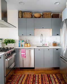 gray kitchen cabinets, kilim rug in kitchen, vintage rug, modern cabinets, flush mount hardware, baskets above cabinets