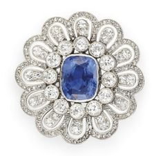 A BELLE EPOQUE SAPPHIRE AND DIAMOND BROOCH   Bezel-set with a cushion-cut sapphire, within a collet-set diamond surround, to the rose and old European-cut diamond daisy motif frame, mounted in platinum, circa 1910