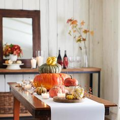 No pumpkin is too small or too big for a stackable centerpiece. (Bonus points for colorful gourds.) See more of our favorite fall centerpieces: www.bhg.com/thanksgiving/indoor-decorating/centerpiece-and-tabletop-decoration-ideas-fall/?socsrc=bhgpin100512colorfulpumpkindisplay#page=18