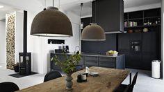 Black kitchen, farmhouse table & industrial pendants