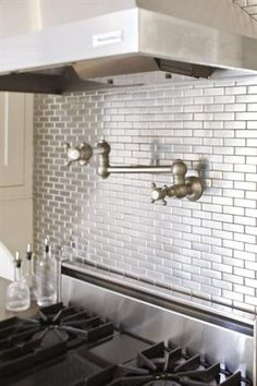 A metallic backsplash adds a contemporary touch to the classic kitchen  www.OakvilleRealEstateOnline.com