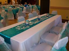White polyester tablecloth with a turquoise runner and White chair covers with turquoise sashes