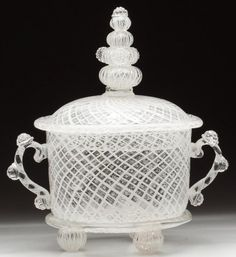 BLOWN LATTICE-AND-BUBBLE BOWL AND COVER, colorless with opal threads, cylindrical bowl with applied ear-like handles and basal ring, raised on three ball feet, cover with four-knop finial, applied prunts, rough pontil marks. 19th or 20th century.