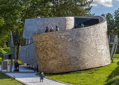 A loosely curving wall of timber shingles spirals around this visitor centre