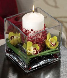 Simple decor with green orchids, candle and bamboo end table