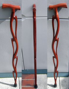 Flame cane Cane.  Carved from African Mahogany wood. Stained a deep red topcoated with clear lacquer, then finished with paste furniture wax for a durable finish.