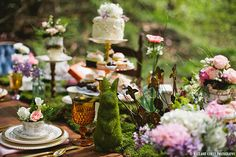 Wedding table centerpieces with a bunny, flowers, cake, and vintage glassware.   Magical Alice In Wonderland Styled Shoot | Justin Alexander Blog