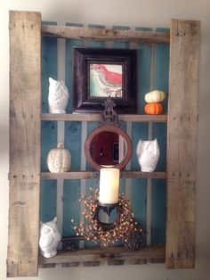 Completed pallet project. So easy to make! Just removed the center board with a crowbar then painted the middle..(almost impaling myself with said crow bar) ...now decorate. Hubby screwed the whole piece to the wall using anchors and a stud finder. I hung a mirrored sconce from Hobby Lobby on one of the nails sticking out from the removed board.