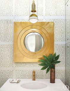 Powder room w/ statement mirror & grid wallpaper (via Architectural Digest)