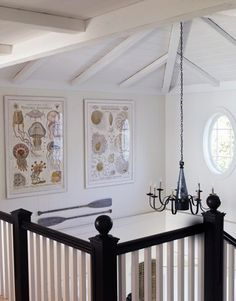 From Slim Paley. Beach house stair railings anchored by black. Black chandelier. Porthole window & beams.